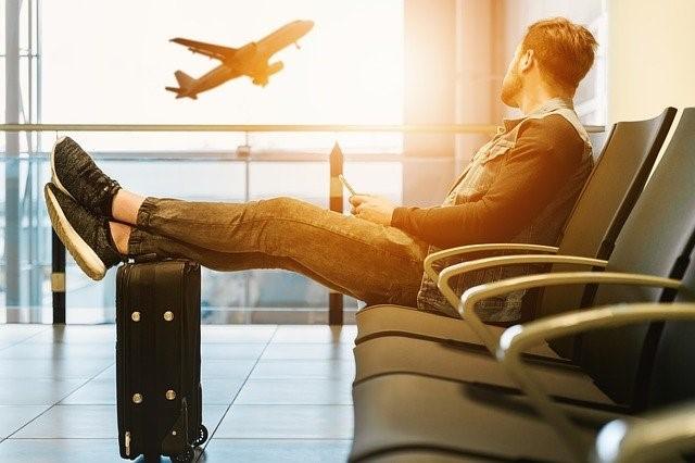 Wartender Passagier blickt auf abhebendes Flugzeug