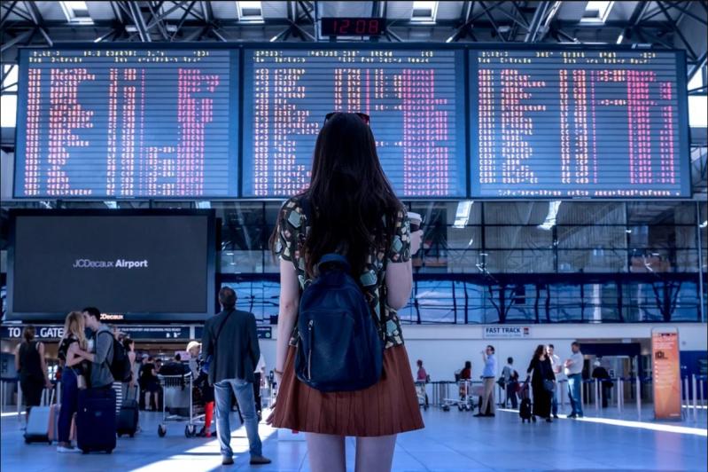 mulher a olhar para a lista de voos no aeroporto